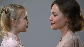 Cabezas que se inclinan de la mamá y de la hija, confiando en relaciones con los padres, confianza almacen de video