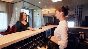 Cabildee a la mujer de negocios de la reunión del recepcionista en la recepción del hotel 4K metrajes