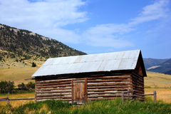 Cabin in Absaroka Mountains. Rustic log cabin, with tin roof, has beautiful backdrop of the Absaroka Mountains in Montana.  Cabin has front door, tin roof and Stock Images