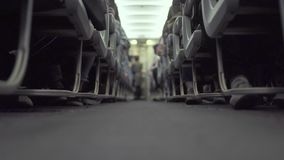 Cabin airplane with passengers sitting on seats and stewardess walking aisle while flying. Passengers on seat in economy. Class commercial aircraft waiting stock footage