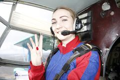 The cabin of an airplane. Pretty girl is sitting on second pilot place. She smiles stock photography