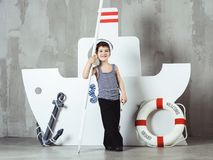 Cabin boy playing with paddle in front of stylized ship. Cute smiling cabin boy in striped t-shirt and sailor cap playing with paddle in front of stylized ship royalty free stock image