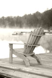 Cabin Chair. An Adirondack chair sits on a dock in Old Forgr, NY.  Softened and dreamy Stock Photo