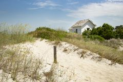 Cabin cottage small house on ocean seashore in grass and sand on a bight sunny day Stock Photo
