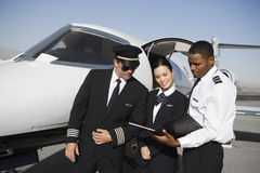 Cabin Crew Members Discussing Reports Together Royalty Free Stock Photo