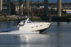 Cabin Cruiser. Yacht speeding down canal royalty free stock photo