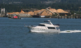 Cabin Cruiser. Boat moving up inner harbour stock photo