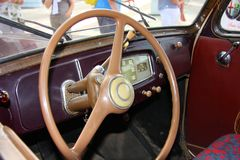 Cabin with dashboard and steering wheel in a vintage car. During a vintage car rally that was held at Chiavari Royalty Free Stock Image