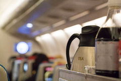 Cabin drinks trolley. Beverage service trolley with tea and soft drinks onboard an Economy class cabin of an airplane Stock Image