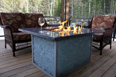 Cabin Fire Pit. Image of a gas fire pit on the deck of a cabin in the mountains stock photo