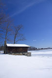 Cabin on frozen lake. Cabin on a frozen lake with a vivid blue sky Royalty Free Stock Image