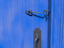Cabin hook latch on a blue door. A simple cabin hook latch holding a blue door closed. Rendered 3d design Royalty Free Stock Image