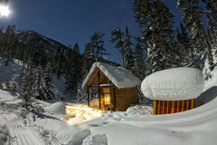 Cabin house chalets in winter forest with snow in light moon and Royalty Free Stock Photography