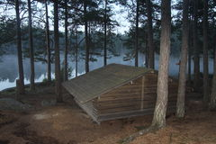 Cabin at lake in early morning. Cabin at the lake in morning hours very early, trees and tree trunks, pine, pines, pine cones on the ground, forest close to the Royalty Free Stock Photo