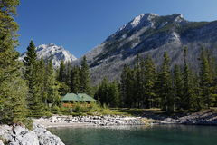 Cabin and Mountain  on Lake Minnewanka. Hicking trails abound on Lake Minnewanka and log cabins offer rest areas Royalty Free Stock Photography