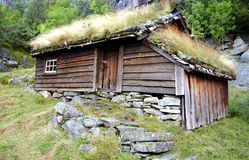 Cabin in the mountains. Old rustic cabin in the mountains with grass roof an stone foundation, taken in the scenic mountains of Norway royalty free stock images