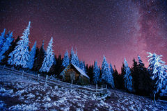 Cabin in the mountains. Fantastic winter meteor rain and snowy m Royalty Free Stock Photo