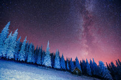 Cabin in the mountains. Fantastic winter meteor rain and snowy m Royalty Free Stock Images