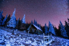 Cabin in the mountains. Fantastic winter meteor rain and snowy m Stock Photos