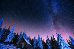 Cabin in the mountains. Fantastic winter meteor rain and snowy m Stock Photography