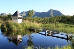 Cabin and mounts mirroring in Lofoten's lake Royalty Free Stock Image