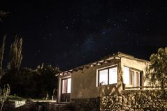 A cabin with a night sky background royalty free stock photo