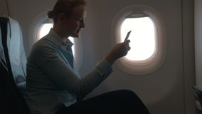 In cabin of plane girl sitting on chair and using mobile terminal on phone and pays for purchase through card stock video
