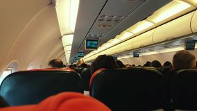 Cabin of the plane with passengers on seat during flight. Izmir, Turkey - December 01, 2017: Interior of airplane with unidentified passengers on seat during stock footage