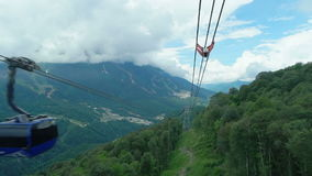 Cabin of ropeway passes over mountains stock footage