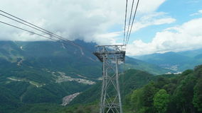 cabin of ropeway passes over mountains stock video footage