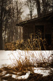 Cabin in the snow. Cabin or shelter in the snow. Grass in the foreground is in sharp focus. the cabin is out of focus with snow falling Royalty Free Stock Photos