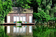 Cabin under trees on waterside Royalty Free Stock Image