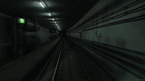 Cabin view of train moving in dark subway tunnel. Train starts moving in dark underground tunnel, cabin view to rail tracks stock footage