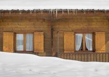 Cabin windows behind snow drift Stock Photo