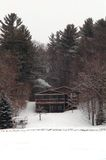 Cabin in the winter. A cabin in northern Minnesota sits upon a hillside nestled between trees. With it snowing outside, a fire burns within the fireplace, smoke Royalty Free Stock Photography
