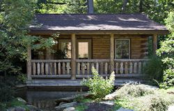 Cabin in the Woods. A log cabin home in the woods. Pond in front - treed lot royalty free stock photo