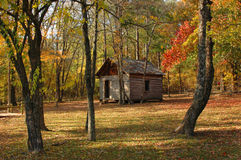 Cabin In The Woods. Old log cabin in the woods in fall stock photography
