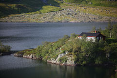 Cabin in the woods beside the lake. In a fjord Stock Photo