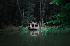 A cabin in the woods by the lake royalty free stock images