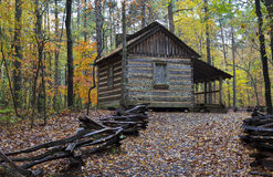 Cabin in the Woods. Log cabin in the fall season with hiking trail royalty free stock photo