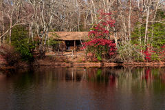 Cabin in the Woods. A log cabin in the woods by a pond and surrounded by colorful foliage in Autumn royalty free stock images