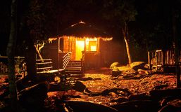 Mawlynnong Meghalaya-Cabin in the woods at night. Night scene of illuminated tiny cabin built of thatch and bamboo in the woods. tungsten light glows brightly in royalty free stock image