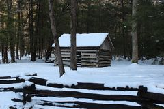 Cabin in woods. Snow covered cabin sits in the woods Stock Photos