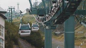 Cabina aérea de la elevación que monta sobre árboles verdes en montañas rocosas almacen de metraje de vídeo