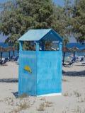 Cabina azul de la alineada en la playa con un juego de natación que cuelga hacia fuera Foto de archivo