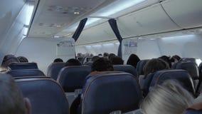 Cabina de aviones de la clase de economía en un aeroplano moderno del pasajero con los pasajeros móviles metrajes