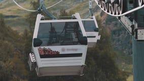 Cabina de la elevación de la góndola que monta sobre árboles verdes en montañas rocosas metrajes