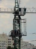 Cabina de la grúa de construcción de la mucha altitud con los trabajadores sobre edificios de la ciudad Imagen de archivo