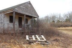 Cabina de madera vieja abandonada del cortijo demasiado grande para su edad con los árboles y las vides Fotografía de archivo libre de regalías