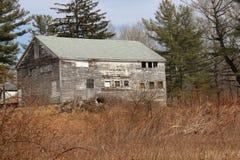 Cabina de madera vieja abandonada del cortijo demasiado grande para su edad con los árboles y las vides Imagen de archivo libre de regalías